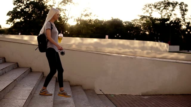 Side view of woman walking with a dog at the leash in the city. Walking down the stairs in the park, holding an orange drink in plastic cup Side view of woman walking with a dog at the leash in the city. Walking down the stairs in the park, holding an orange drink in plastic cup. leash stock videos & royalty-free footage