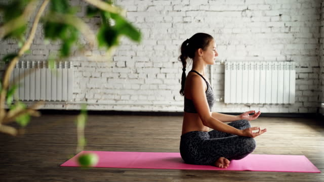 side view of yoga student relaxing and breathing while sitting in lotus position on bright mat. attractive woman is having rest after long practice in wellness center. - posizione corretta video stock e b–roll