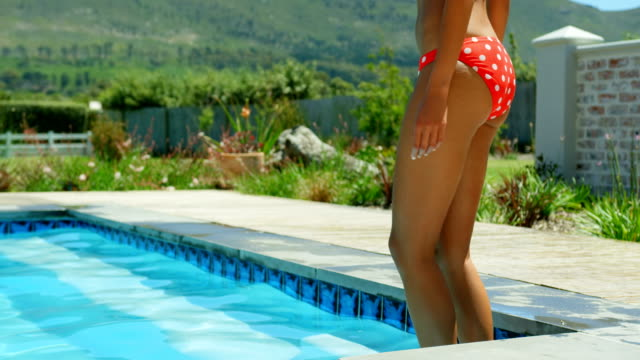 Side view of young black woman walking in the swimming pool at resort 4k