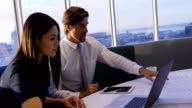istock Side view of young Caucasian office executives working on laptop and blueprint at table in office 4k 1146880264
