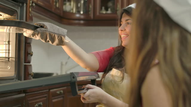 vídeos de stock e filmes b-roll de side view of young caucasian woman opening electric oven and taking off fresh baked buns. mother blowing on hot cookies and her daughter clapping hands. cinema 4k footage prores hq. - assado no forno