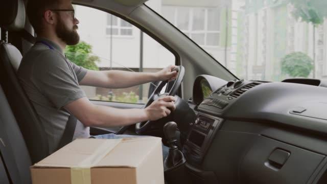 帶紙盒的年輕快遞駕駛汽車的側視圖 - postal worker 個影片檔及 b 捲影像