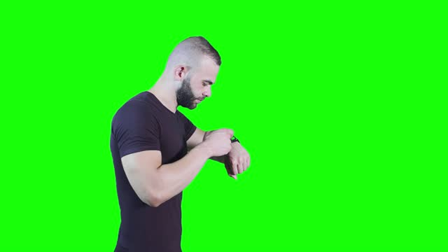 Side view of young man using smartwatch against green background