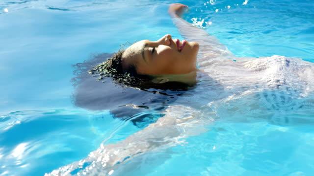 vídeos de stock, filmes e b-roll de opinião lateral a mulher nova da misturado-raça que flutua na piscina em um dia ensolarado 4k - flutuando na água