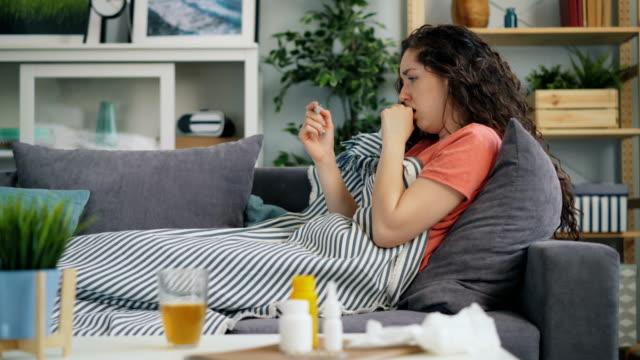 stockvideo's en b-roll-footage met zijaanzicht van jonge vrouw die temperatuur met thermometer in huis op sofa - thermometer