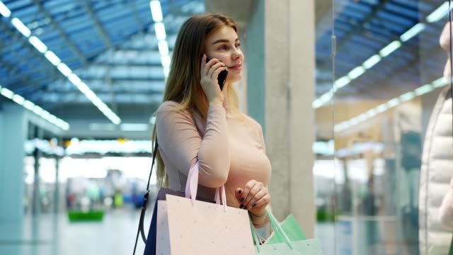 Side view of young woman with shopping bags standing by window display in shopping center, looking at outfits on mannequins and talking on cellphone asking her boyfriend for money, then kissing phone
