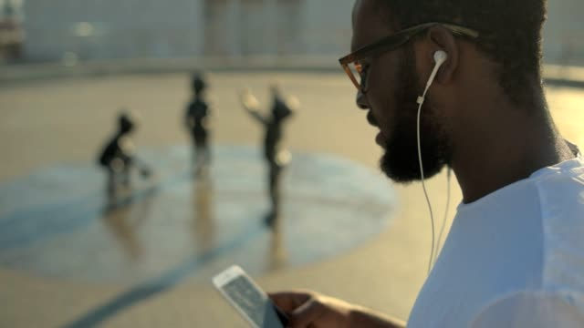 Side view on African American guy listening to music outdoors Music in my veins. Bearded young guy wearing glasses enjoying the music while walking around and relaxing outdoors. headphones stock videos & royalty-free footage