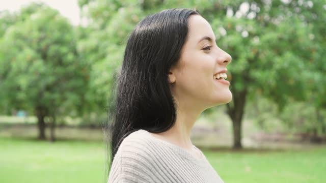 yan görünümü taze havayı rahatlatıcı parkta genç bir kadın portresi - rahatlama stok videoları ve detay görüntü çekimi