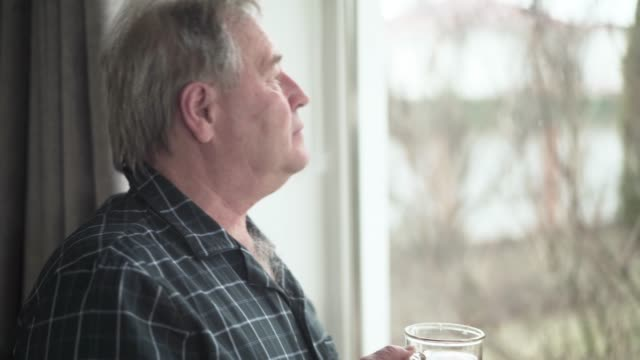 vídeos de stock e filmes b-roll de side view portrait of thoughtful senior caucasian man looking out the window and drinking tea indoors. lonely male retiree waking up in the morning at home. lifestyle, leisure, retirement, aging. - old men window