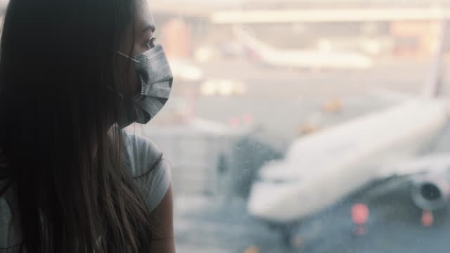 Side view, portrait of woman in protective mask looks in airport window COVID-19