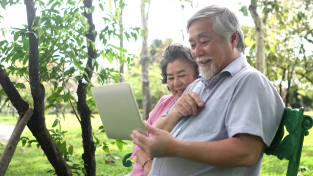 side view : Senior Asian couple are exciting to use notebook video