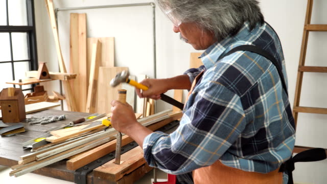 side view: senior carpenter carving on wood in the workshop house