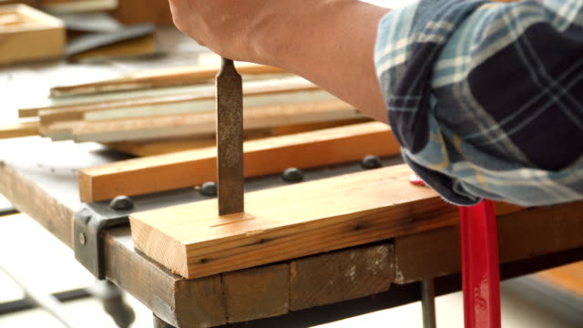 side view: senior carpenter's hand carving on wood in the workshop house