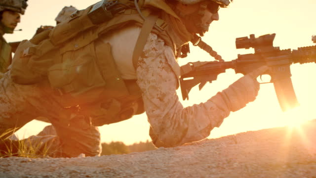 Side view Soldiers Lie Down on the Hill, Aim through the Assault Rifle Scope in Desert Environment in Sunset Light. Slow Motion. video