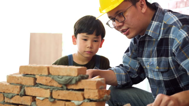 side view: son use hammer and level to make brick having level by himself with Construction father's help on a new house