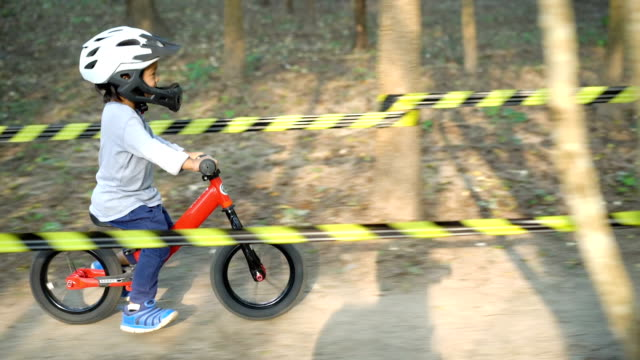 Side view Toddler riding balance bike on dirt road.