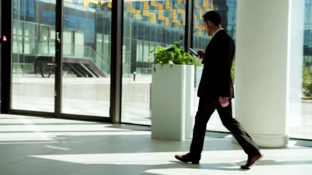 side view tracking left shot of middle aged manager in black suit text messaging on smartphone while walking along entrance hall in modern business center and finally entering door - wchodzić filmów i materiałów b-roll