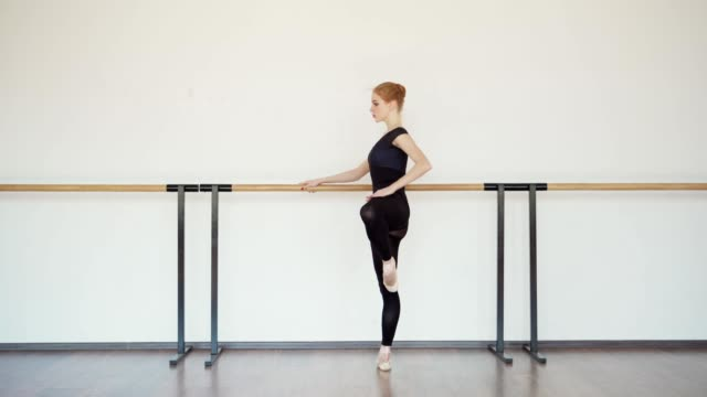 side view tracking shot of beautiful young ballerina stretching at barre in ballet studio - rozgrzewka filmów i materiałów b-roll