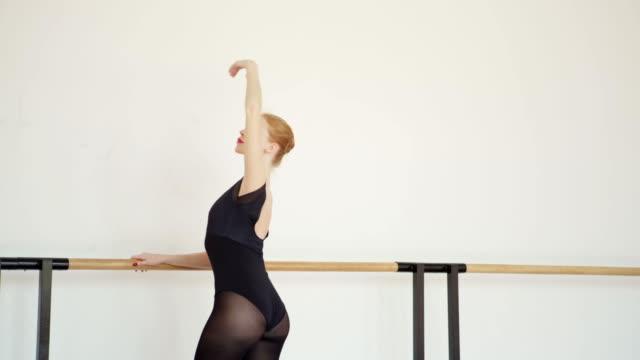 side view tracking aufnahme von anmutigen weiblichen balletttänzerin in schwarzem trikot üben port de bras bei barre im ballettstudio - gymnastikanzug stock-videos und b-roll-filmmaterial