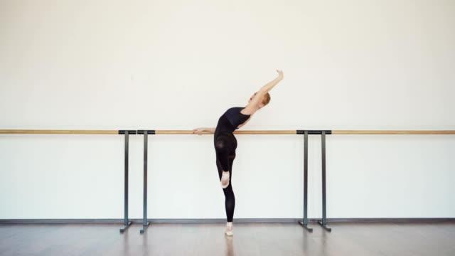 side view tracking aufnahme von anmutigen lesekopf junge ballerina in schwarzem trikot üben bei barre im ballettstudio - gymnastikanzug stock-videos und b-roll-filmmaterial