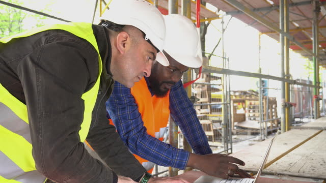 vídeos de stock, filmes e b-roll de vista lateral: dois engenheiros em computador em local de construção entre andaimes - eletricista