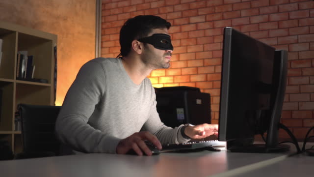 Side view: Unrecognizable computer hacker or spy with a black mask using computer PC late at night in a modern office, passing network security and privacy, searching and stealing e-mail, business, and intellectual property.