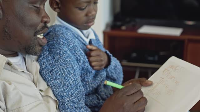 side view video av farfar att hjälpa hans sonson med läxor - stavning bildbanksvideor och videomaterial från bakom kulisserna