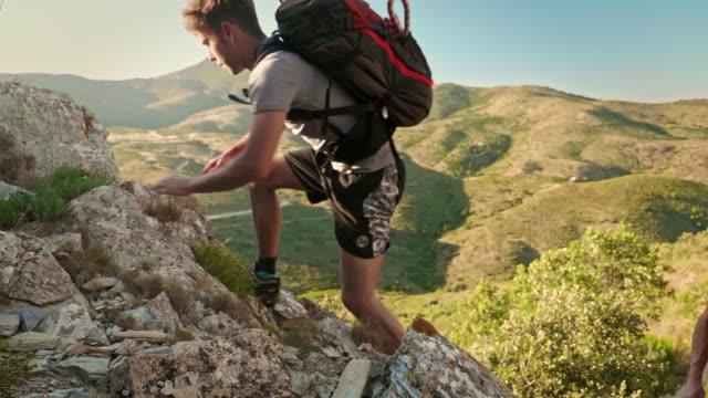 vidéos et rushes de vue latérale vidéo du fils et de son père escaladant une montagne au coucher du soleil - 20 24 ans
