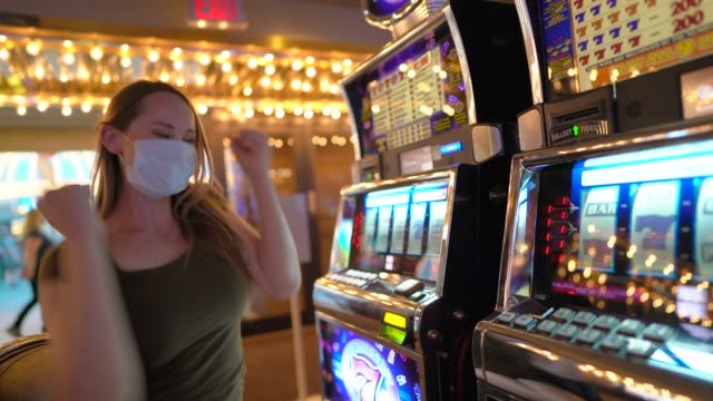 side view woman plays slots with face mask at casino and wins big, celebrates