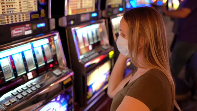 side view woman plays slots with face mask during COVID-19 at casino and winning video