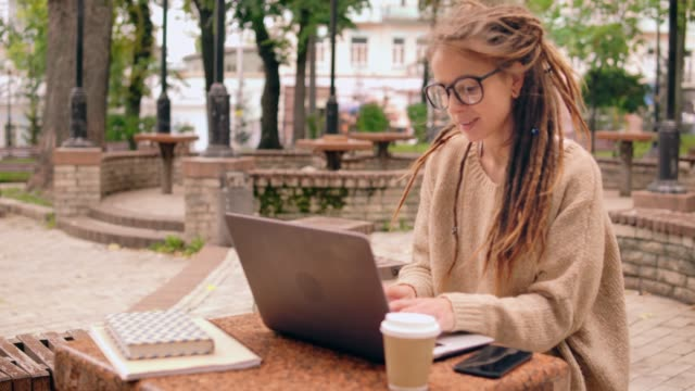 side view young girl works outdoors smiling caucasian woman with dreadlocks and eyeglasses sitting in autumn park. busy freelancer typing on laptop using smartphone locs hairstyle stock videos & royalty-free footage