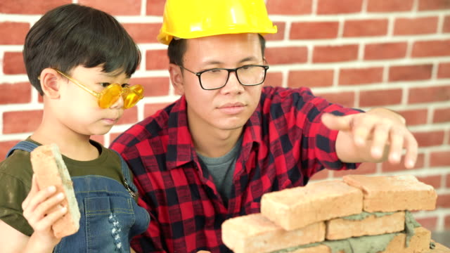 Side view:son try to lay brick by himself with Construction father's help on a new house