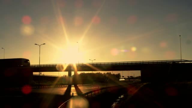 sida-vy av en vit semi truck med cargo trailer körning över en bro. vacker natur med fordonet i rörelse på överfart. det blir mörkt och solen är inställningen. - shipping sunset bildbanksvideor och videomaterial från bakom kulisserna