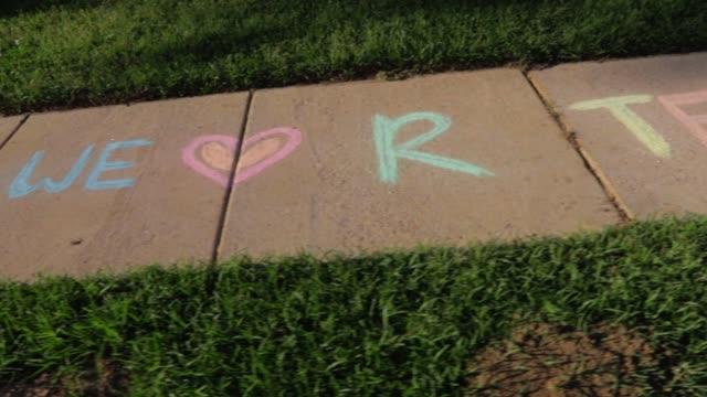 "sidvideo walk delle parole ""we love our teachers"" disegnate con gesso sul marciapiede.ww - marciapiede video stock e b–roll"
