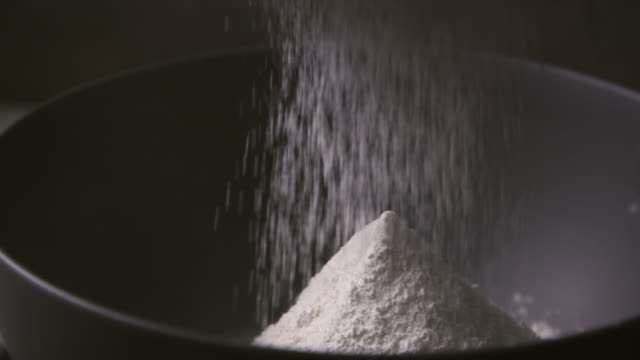 Sieving flour Sieving flour into a mixing bowl mixing bowl stock videos & royalty-free footage
