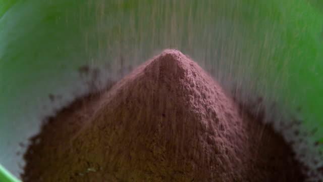 vídeos de stock e filmes b-roll de sifting cocoa powder to make pastry dough - cacau em pó