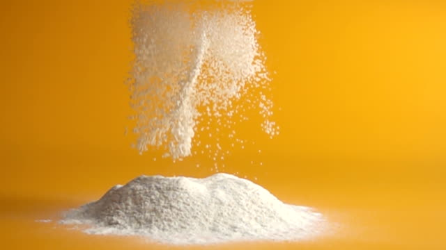 sifting flour in slow motion sifting flour and falling in slow motion on to a yellow counter top stock footage flour stock videos & royalty-free footage