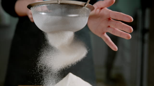 SLO MO CU Sifting the flour Super slow motion close up shot of an unrecognizable woman sifting the flour on the table. flour stock videos & royalty-free footage