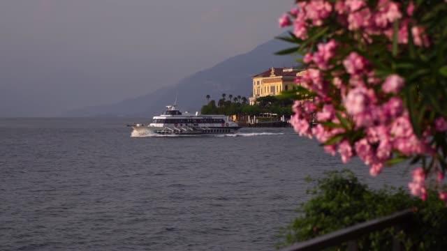 sightseeing boat ship leaving bellagio, lake como. - lombardia video stock e b–roll