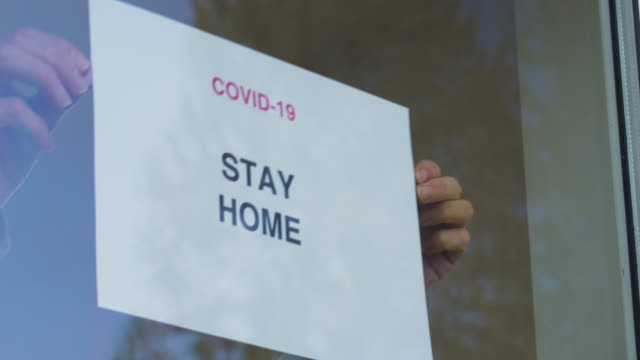 STAY HOME sign being applied to window. Coronavirus measures. 4K resolution. stay home stock videos & royalty-free footage