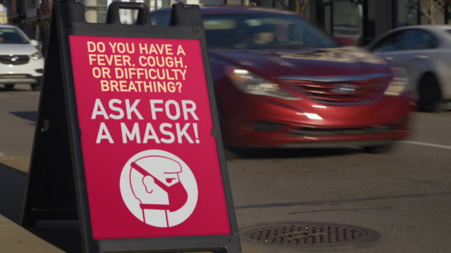 Sign in Business District Tells Customers to Ask for a Mask A sign outside of a store in a city's business district informs customers and pedestrians to ask for a face mask if they are experiencing a cough, fever, or have breathing problems to help the spread of Coronavirus COVID-19. emphysema stock videos & royalty-free footage