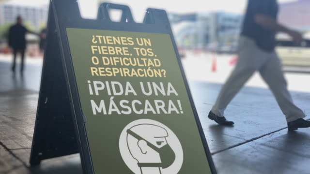 Sign in Busy Public Area Informs Pedestrians to Ask for a Mask video