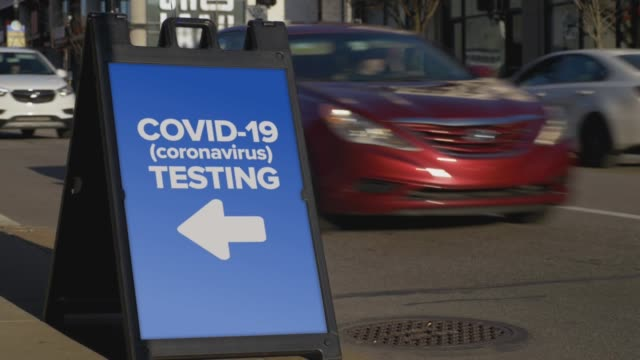 sign in city shows where to get coronavirus testing - covid testing стоковые видео и кадры b-roll