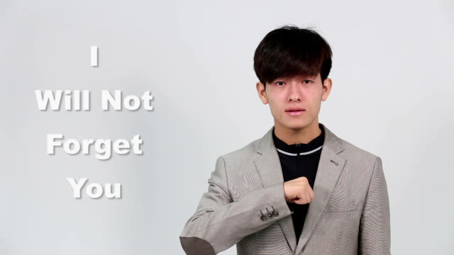 Sign Language by Asian Man in Suit Jacket over Gray Background, Mean 'I will not Forget You' video