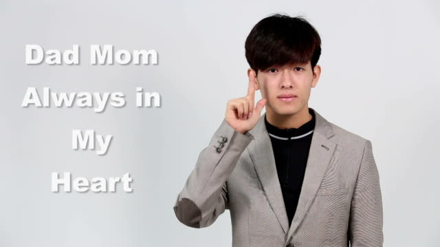 Sign Language by Asian Man in Suit Jacket over Gray Background, Mean 'Dad Mom Always in my Heart' video