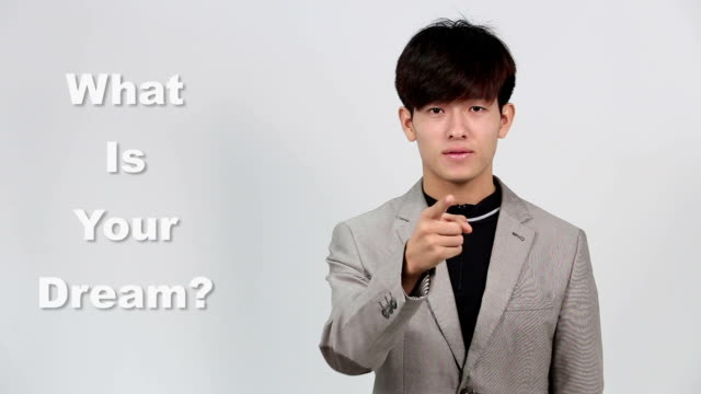 Sign Language by Asian Man in Suit Jacket over Gray Background, Mean 'What is your Dream' video