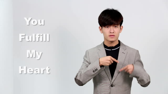 Sign Language by Asian Man in Suit Jacket over Gray Background, Mean 'You Fulfill my Heart' video