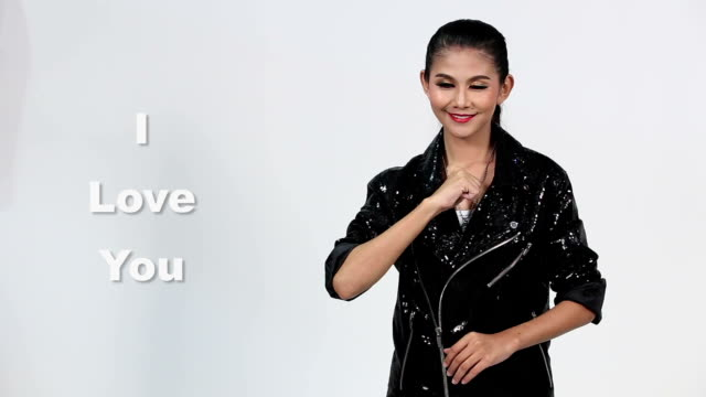 Sign Language by Asian woman in Suit Jacket over Gray Background, Mean 'I Love You' video