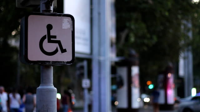 vídeos de stock e filmes b-roll de sign of a disabled person sitting on a wheelchair against the background of blurred walking people. concept idea - badge