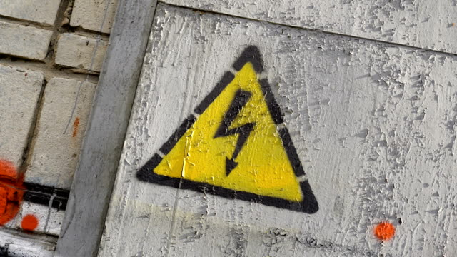 Sign of danger electric shock rotate. Yellow designation of high voltage on door Sign of danger of electric shock rotates close-up rotate. Yellow designation of high voltage on the door close-up spin. Old age generalized kraaska. Dirty building 4k swirling. Sign danger and caution high voltage sign stock videos & royalty-free footage